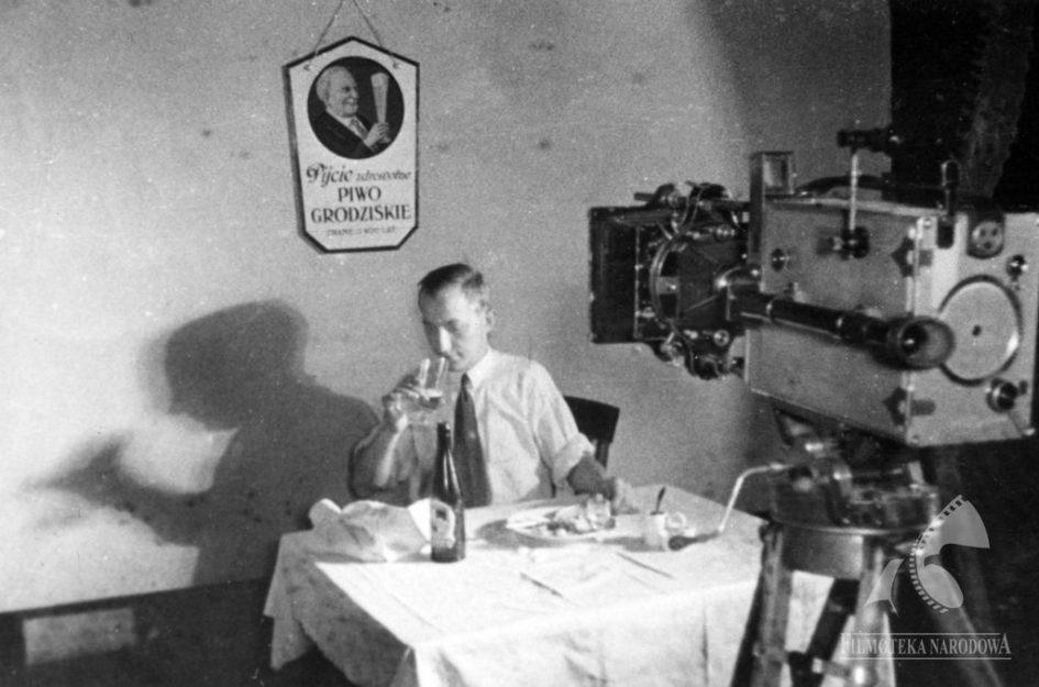 """""""10% dla mnie"""", 1933, Na zdjęciu: Feliks Matuszelański, asystent operatora, reklama piwa Grodziskiego, butelka piwa Jane Pełne z browaru Haberbusch i Schiele. Źródło: fototeka.fn.org.pl"""